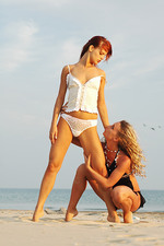 Two beautiful babes kissing on the beach 00
