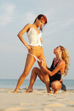 Two beautiful babes kissing on the beach 01