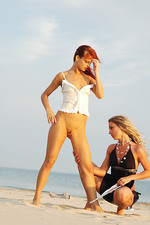 Two beautiful babes kissing on the beach 02
